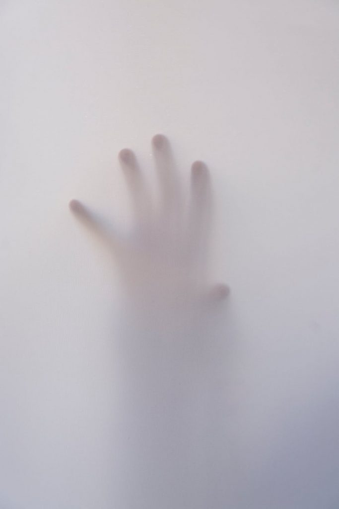 a hand against the glass