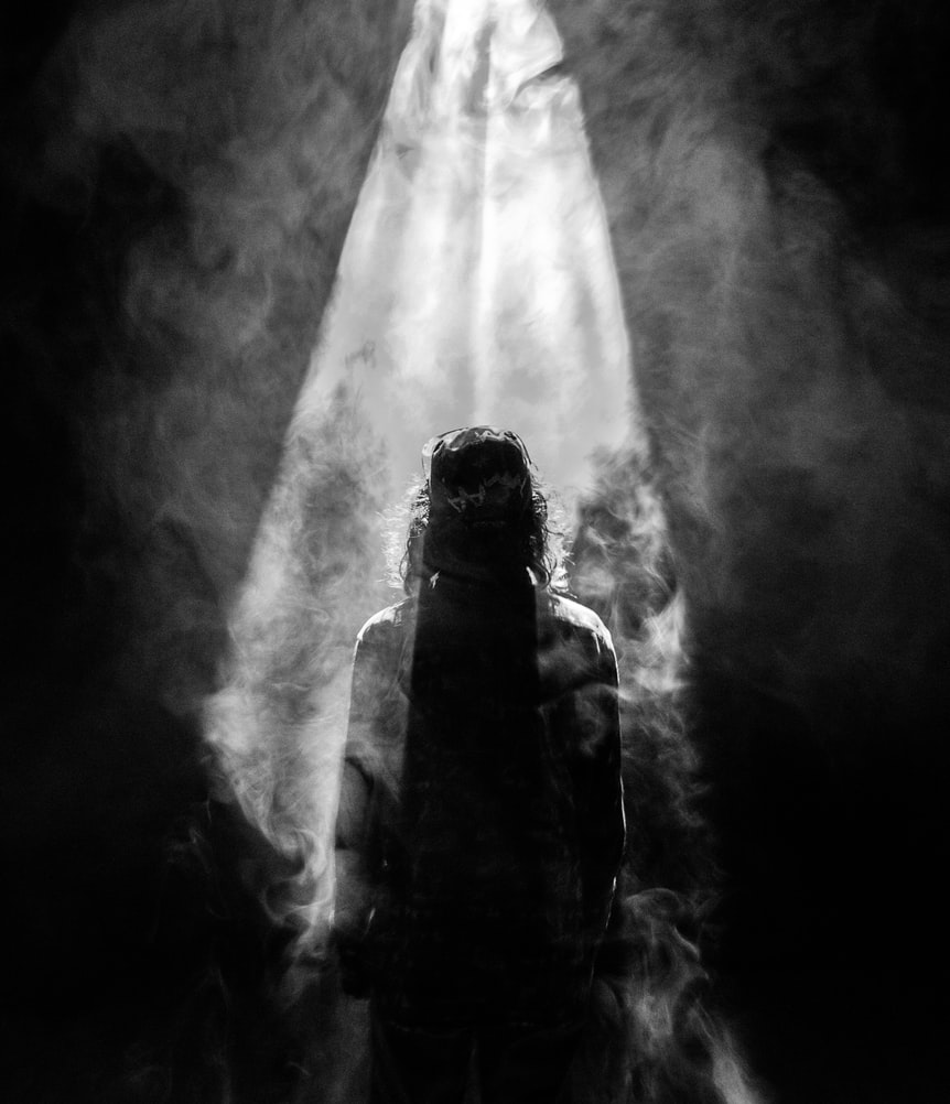 light shining down on a woman in a smoky room
