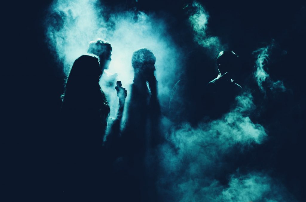 people silhouetted in a smoky room