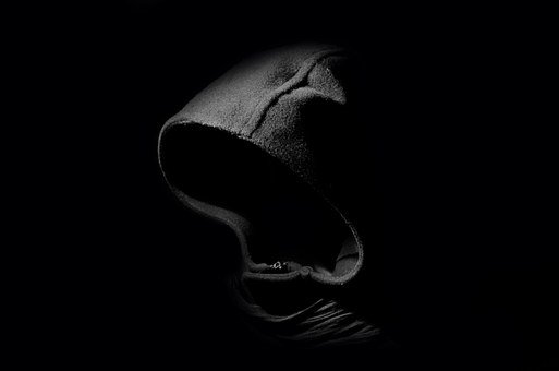 image shows a shadowy figure with a hood